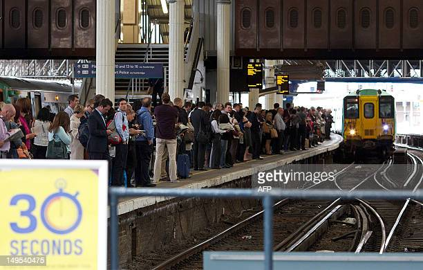 Passengers wait for trains on a platform at London Bridge Station in London on July 30 on the first weekday of the London 2012 Olympic Games AFP...