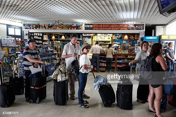 Passengers wait in a queue to check in for their flights in the departures hall at Santorini airport on the island of Santorini Greece on Thursday...