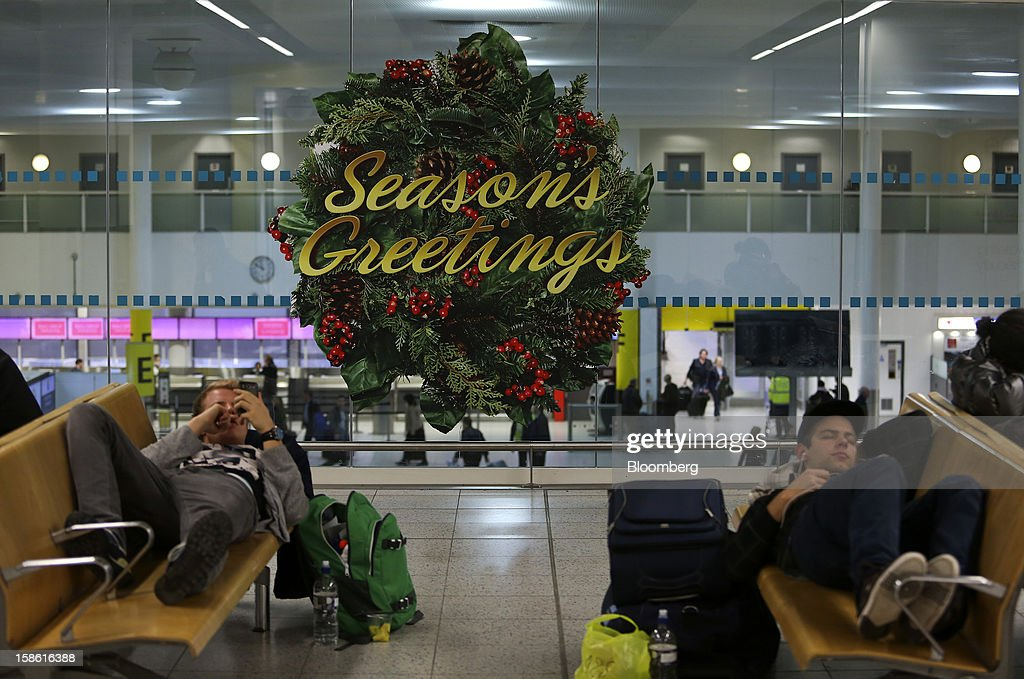 Passengers wait in a seating area near a giant 'Seasons Greetings' Christmas wreath hanging on a glass wall in the south terminal at Gatwick airport in Crawley, U.K., on Friday, Dec. 21, 2012. U.K. airports predicted today to be the busiest day during the Christmas period, as some Britons opt to spend the holidays abroad and overseas visitors fly out to be with friends and family. Photographer: Chris Ratcliffe/Bloomberg via Getty Images