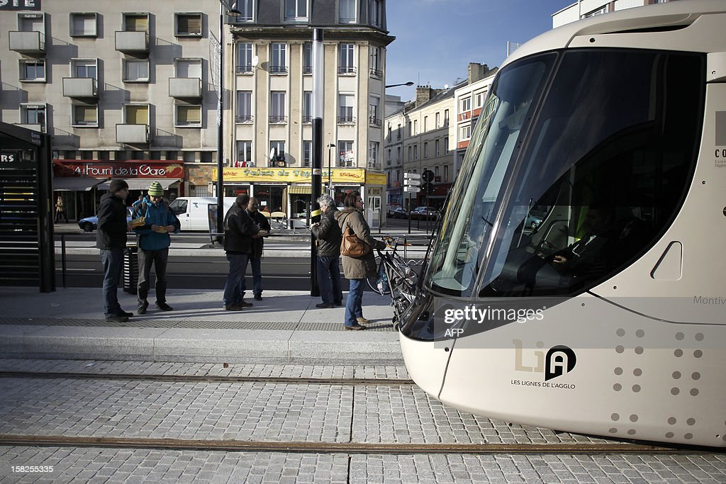 Passengers wait, in front of the railway station, to enter the tramway during its inaugural day, on December 12, 2012 in the northwestern city of Le Havre. 23 stations serve the 13 km network whom carriages have been made by French engineering giant Alstom. AFP PHOTO/CHARLY TRIBALLEAU.