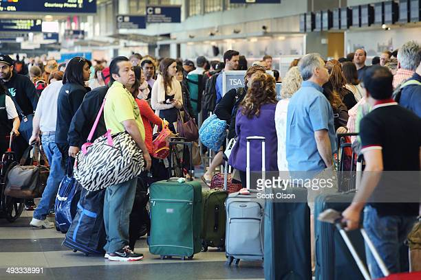 Passengers wait in line at a security checkpoint at O'Hare Airport May 23 2014 in Chicago Illinois Chicago's O'Hare and Midway International Airports...