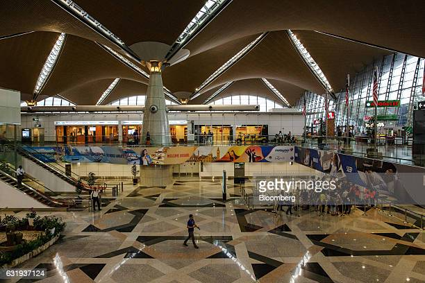 Passengers wait in line at an immigration counter at Kuala Lumpur International Airport in Sepang Selangor Malaysia on Tuesday Jan 17 2017 The hunt...