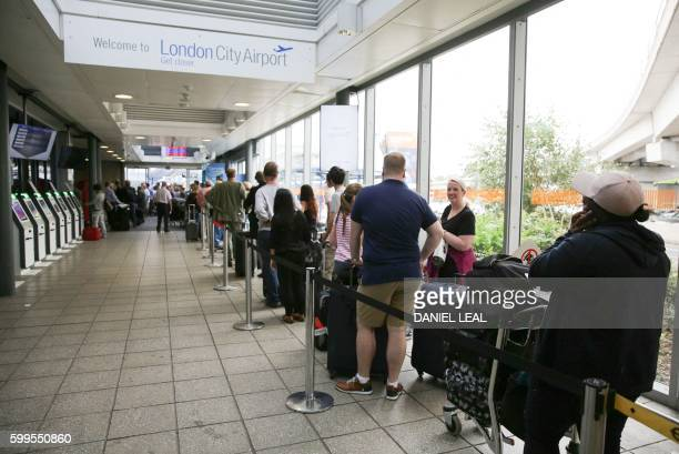 Passengers wait in line at London City Airport in London after protestors blocked the runway and caused all the flights from the airport to be...