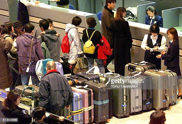 Passengers wait in line in front of a checkin counter at the Narita International Airport suburb of Tokyo 25 December 1999 The numbers of Japanese...