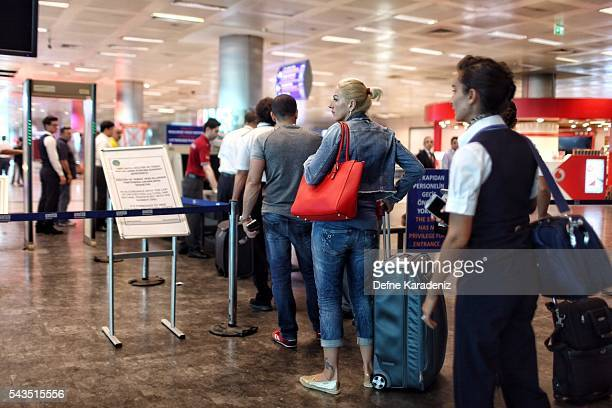 Passengers wait in line in front of an xray machine at a security check point at Turkey's largest airport Istanbul Ataturk following yesterday's...