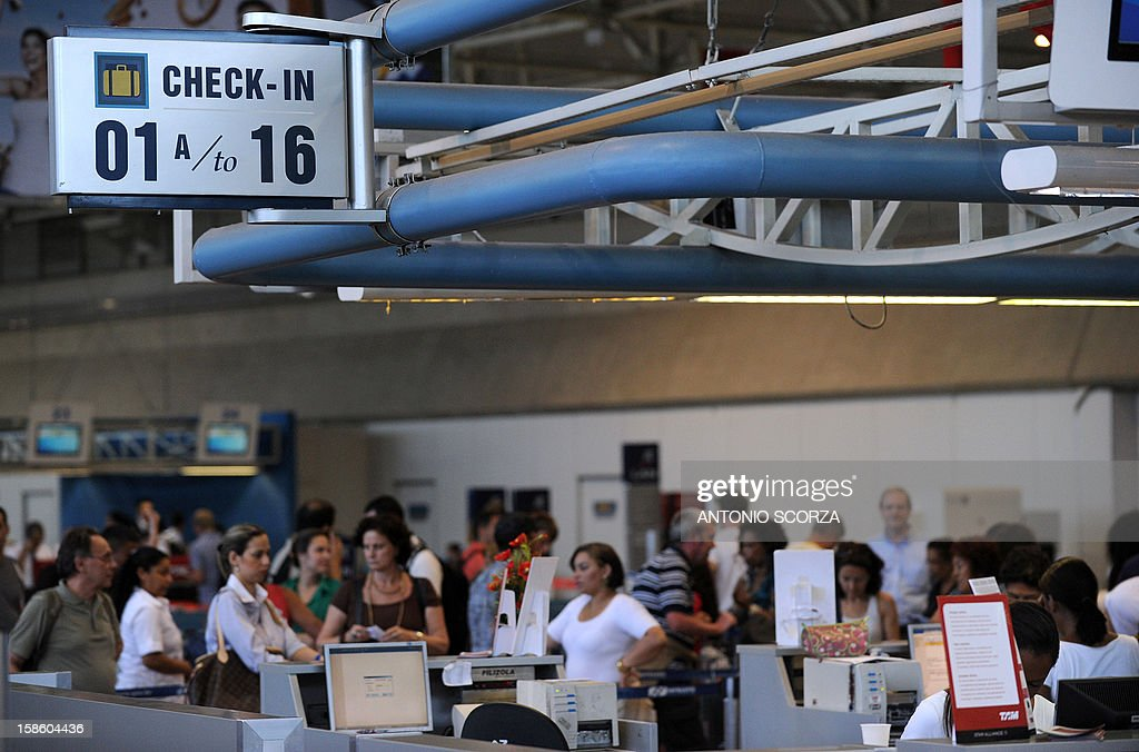 Passengers wait in line to check-in to their flights at the Antonio Carlos Jobim international airport in Rio de Janeiro, Brazil on December 20, 2012. Brazilian President Dilma Rousseff on Thursday announced that airports in Rio and Belo Horizonte, two host cities for the 2014 World Cup, would be privatized during a September 2013 auction. AFP PHOTO/ANTONIO SCORZA