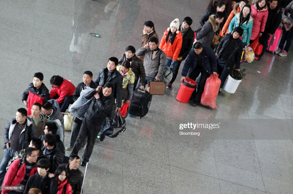 Passengers wait in line to enter Hongqiao Railway Station in Shanghai, China, on Sunday, Feb. 3, 2013. Forecasts of snow and rain across China threaten to disrupt the travel plans of millions of Chinese heading home for the Lunar New Year holidays that start Feb. 9, the national weather agency warned. Photographer: Tomohiro Ohsumi/Bloomberg via Getty Images