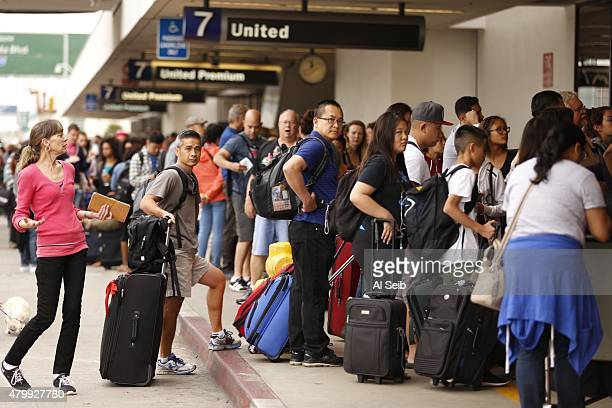 Passengers wait in long lines at the United Airlines terminal at LAX in the morning after a nationwide flight stoppage July 8 2015 in Los Angeles...