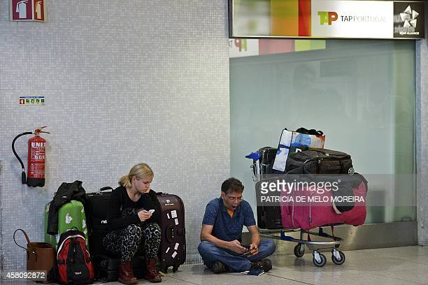 Passengers wait near a Portugese airline TAP customer service desk at Lisbon's airport during a strike on October 30 2014 Air traffic was disrupted...