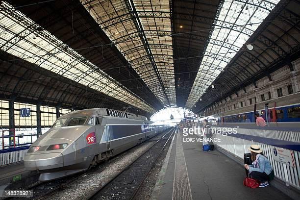 Passengers wait on a platform as a TGV highspeed train arrives at SaintJean railway station in Bordeaux southwestern France on July 9 2012