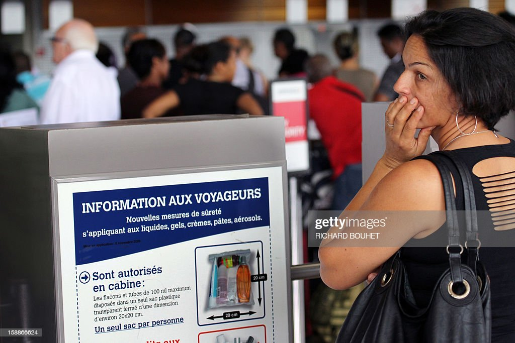 Passengers wait, on January 2, 2013 at Gillot airport in Sainte-Marie de la Reunion, a French island located in the Indian Ocean, as the airport is to shut down as tropical storm Dumile is forecast to strike the island as a tropical cyclone later today. AFP PHOTO RICHARD BOUHET