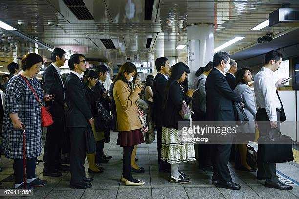 Passengers wait on the platform for a train on the Marunouchi subway line operated by Tokyo Metro Co during the morning rush hour at Shinjuku station...