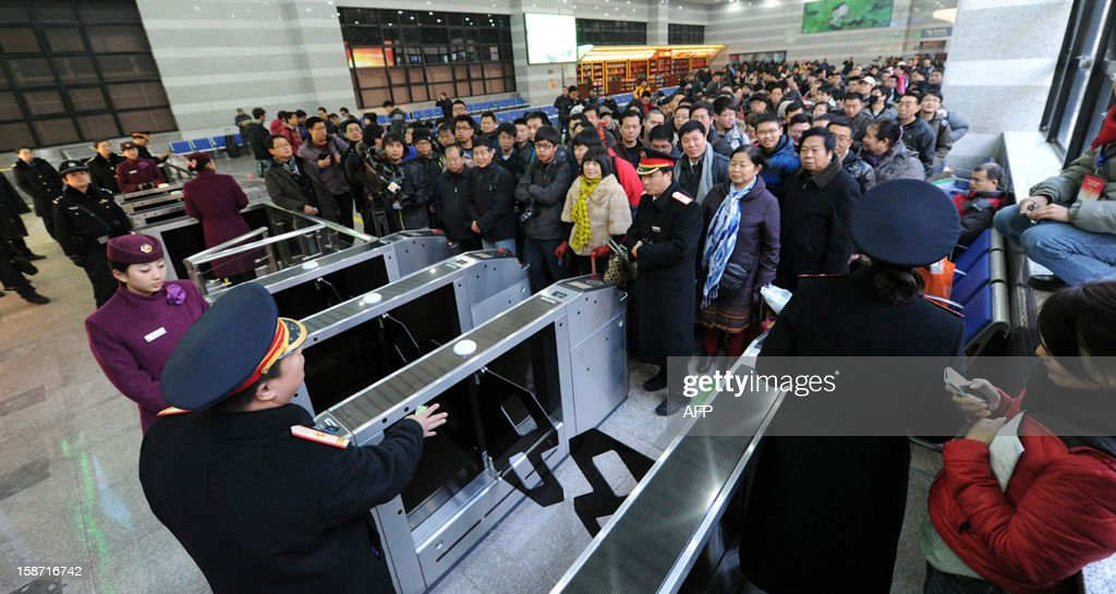 Passengers wait outside the ticket gate before boarding on the new 2,298-kilometre (1,425-mile) line between Beijing and Guangzhou in Beijing on December 26, 2012. China started service on December 26 on the world's longest high-speed rail route, the latest milestone in the country's rapid and -- sometimes troubled -- super fast rail network. The opening of this new line means passengers will be whisked from the capital to the southern commercial hub in just eight hours, compared with the 22 hours previously required. CHINA