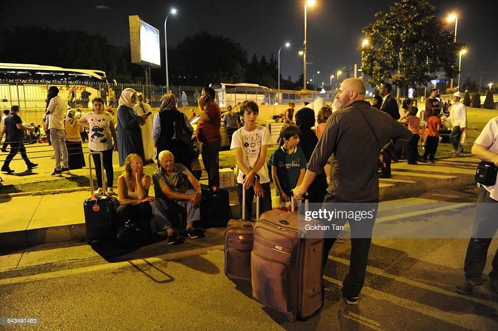 Passengers wait outside the Turkey's largest airport, Istanbul Ataturk after the suicide bomb attacks, June 28, 2016, Turkey. Three suicide bombers opened fire before blowing themselves up at the entrance to the main international airport in Istanbul, killing at least 28 people and wounding at least 60 people according to Istanbul governor Vasip Sahin.