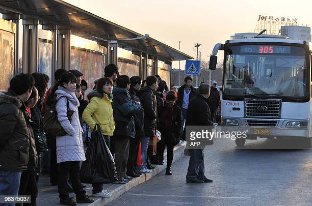 Passengers wait to board a bus at a stop in Beijing on February 1 2010 AFP PHOTO/OLLI GEIBEL