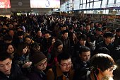 Passengers wait to board a train at Beijing West Railway Station on February 13 2015 Millions of Chinese are making journeys to their hometowns for...
