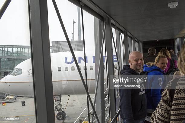Passengers wait to board a United Airlines flight to New York at the Oslo Airport Gardermoen March 9 2013 in Oslo Norway Gardermoen is the main...