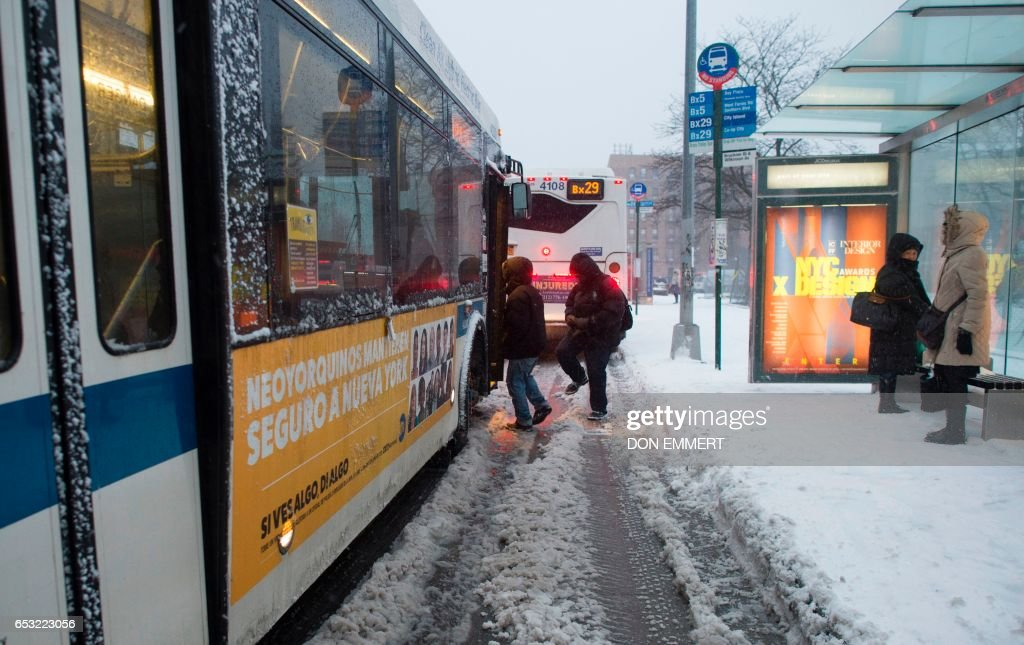 Passengers wait to board buses in the Bronx Borough March 14, 2017 in New York. Winter Storm Stella dumped snow and sleet Tuesday across the northeastern United States where thousands of flights were canceled and schools closed, but appeared less severe than initially forecast. After daybreak the National Weather Service (NWS) revised down its predicted snow accumulation for the city of New York, saying that the storm had moved across the coast. EMMERT