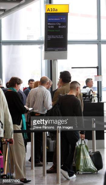 Passengers wait to board the British Airways flight to Mexico City at Heathrow Airport in Middlesex