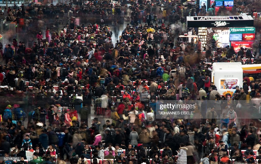 TOPSHOT Passengers wait to board their trains as they head to their hometown for the Lunar New Year holiday at Shanghai Hongqiao railway station in...