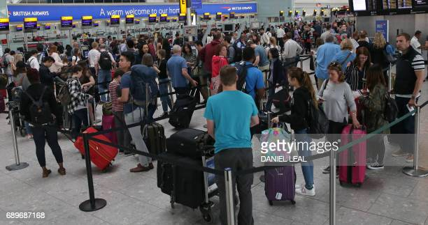 Passengers wait to checkin at a British Airways desk inside Terminal 5 of London's Heathrow Airport on May 29 2017 Passengers faced a third day of...