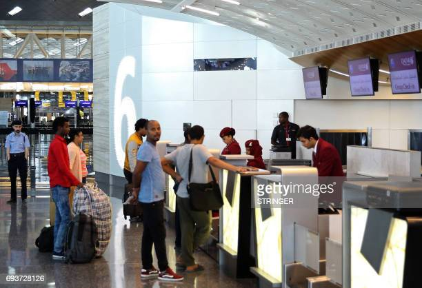 Passengers wait to checkin at the Qatar Airways Hamad International Airport in Doha on June 7 2017 A ban on Qatari flights imposed by Saudi Arabia...
