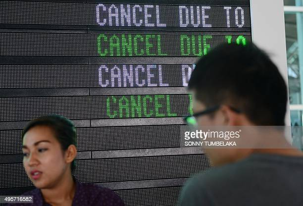 Passengers wait to obtain information on delayed and cancelled flights at the international departure area of Bali's Ngurah Rai Airport in Denpasar...