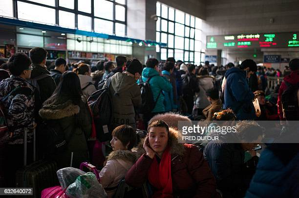 Passengers wait to take their trains back to their hometowns for the 'Spring Festival' or Lunar New Year from the Beijing West Railway Station in...