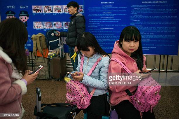 Passengers wait to travel back to their hometowns for the 'Spring Festival' or Lunar New Year from the Beijing West Railway Station in Beijing on...