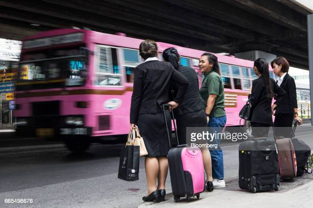 Passengers wait with their luggage at a bus stop in the Phaya Thai District of Bangkok Thailand on Wednesday April 5 2017 The central...