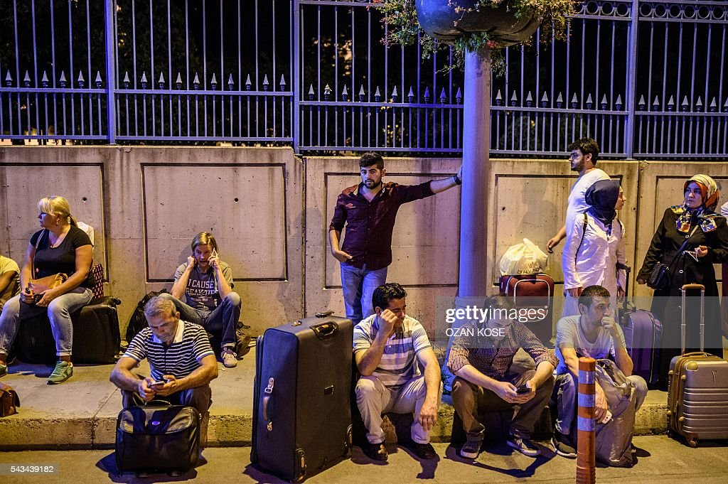 Passengers wait with their luggage outside the Ataturk airport in Istanbul, on June 28, 2016, after two explosions followed by gunfire hit the Turkey's biggest airport, killing at least 10 people and injured 20. All flights at Istanbul's Ataturk international airport were suspended on June 28, 2016 after a suicide attack left at least 10 people dead and 20 others wounded, Turkish television stations reported. / AFP / OZAN