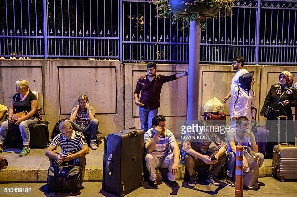 Passengers wait with their luggage outside the Ataturk airport in Istanbul on June 28 after two explosions followed by gunfire hit the Turkey's...