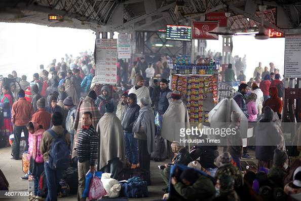 Passengers waiting for the train in a chilly morning at New Delhi Railway Station on December 22 2014 in New Delhi India Dense fog reduced visibility...
