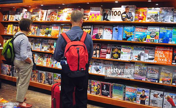 Passengers waiting for their flights peruse a selection of magazines in a shop inside San Francisco International Airport