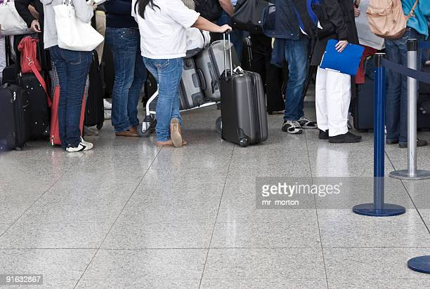 Passengers waiting in line to check in with luggage