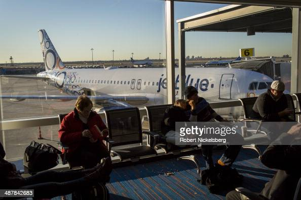 Passengers waiting to fly on a JetBlue Airways plane sit in a lounge April 1 2014 at John F Kennedy International Airport in Queens New York