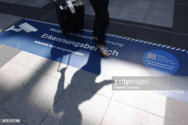 Passengers walk by a security sign warning for a Face recognition area at the Suedkreuz train station on August 1 2017 in Berlin Germany German...