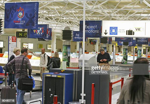 Passengers walk by as UEFA EURO 2008 posters hang over the terminal's sealing at the airport in Schwechat some 25 kilometers east from Vienna on...