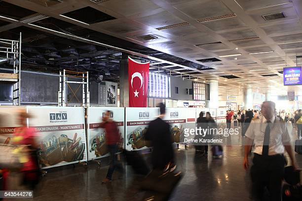 Passengers walk in the damaged parts of the international terminal of the country's largest airport Istanbul Ataturk following yesterday's blast on...
