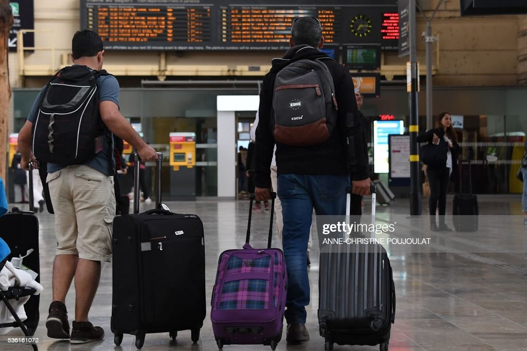 Passengers walk in the Saint-Charles rail station in Marseille, southeastern France, on May 31, 2016, at the start of a strike by employees of French state-owned rail operator SNCF to protest against government labour reforms. France is bracing for a week of severe disruption to transport after unions called for more action in their bitter standoff with the Socialist government over its labour market reforms. / AFP / ANNE