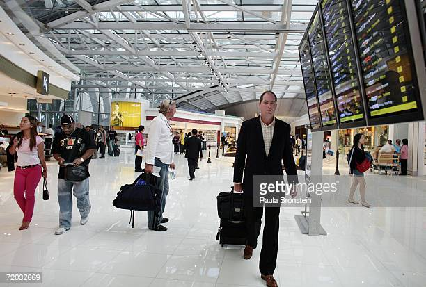 Passengers walk inside the Duty Free area in the departure level at Bangkok's Suvarnabhumi Airport during its first full day of operation September...