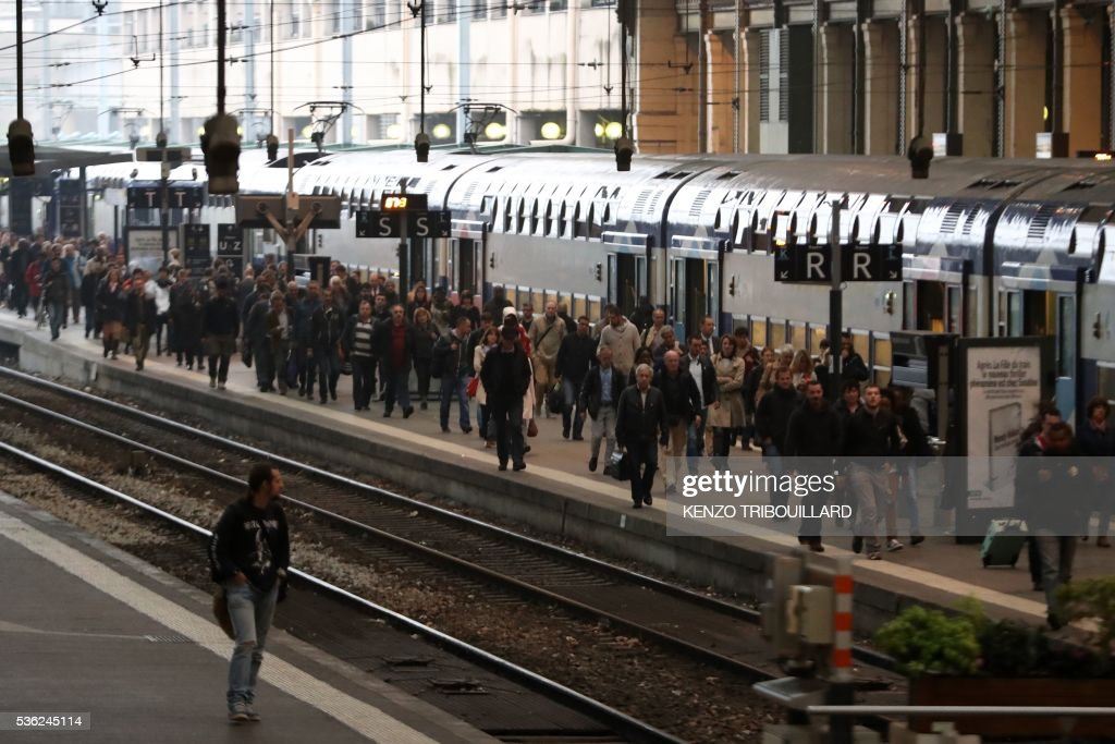 Passengers walk on a platform at the Gare de Lyon railway station on June 1, 2016 in Paris, at the start of a strike by employees of French state-owned rail operator SNCF to protest against government labour reforms. Rail strikes in France are expected to take full effect, disrupting transport across the country just over a week before the Euro 2016 football championship starts. / AFP / KENZO
