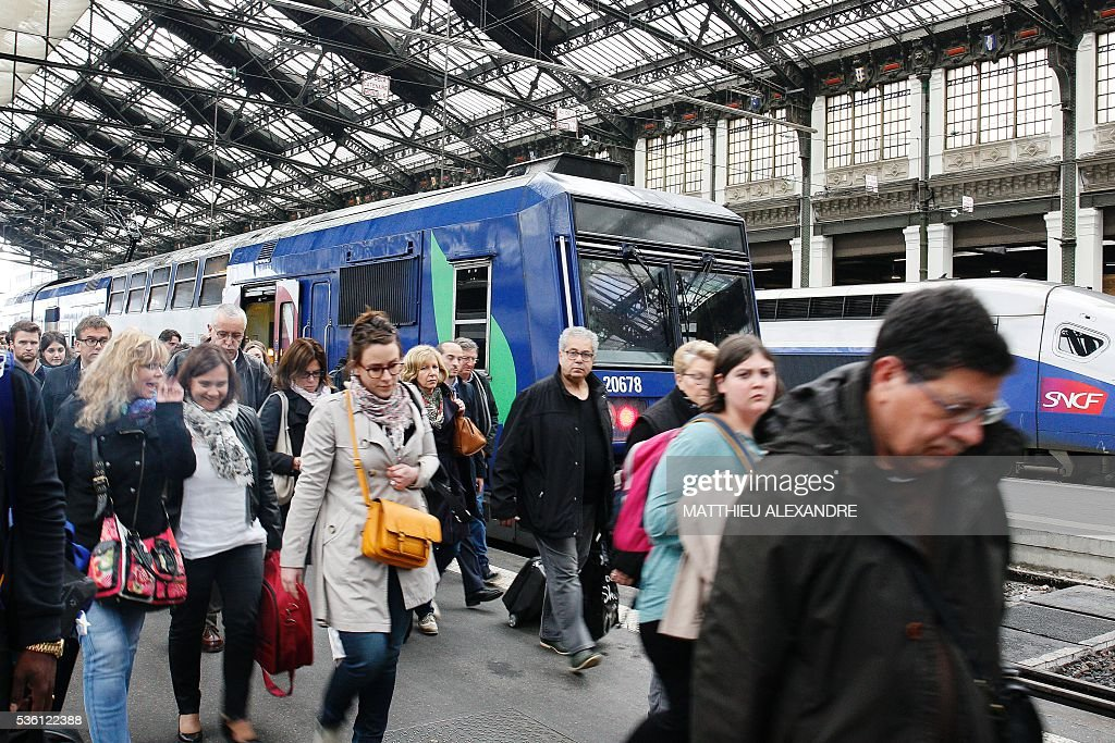 Passengers walk on a platform in the Gare de Lyon rail station in Paris, on May 31, 2016, a few hours prior to the start of a strike by employees of French state-owned rail operator SNCF to protest against government labour reforms. France is bracing for a week of severe disruption to transport after unions called for more action in their bitter standoff with the Socialist government over its labour market reforms. / AFP / MATTHIEU