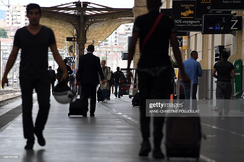 Passengers walk on a platform in the Saint-Charles rail station in Marseille, southeastern France, on May 31, 2016, at the start of a strike by employees of French state-owned rail operator SNCF to protest against government labour reforms. France is bracing for a week of severe disruption to transport after unions called for more action in their bitter standoff with the Socialist government over its labour market reforms. / AFP / ANNE