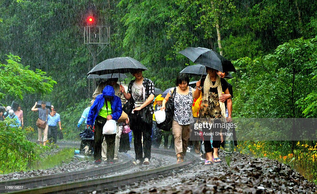 Passengers walk on the railway track in the heavy rain on August 18, 2013 in Mori, Hokkaido, Japan. Train operation between Sapporo and Hakodate has been suspended due to a landslide triggered by a torrential rain washed the enbankment, hit 'bon' holidaymakers.