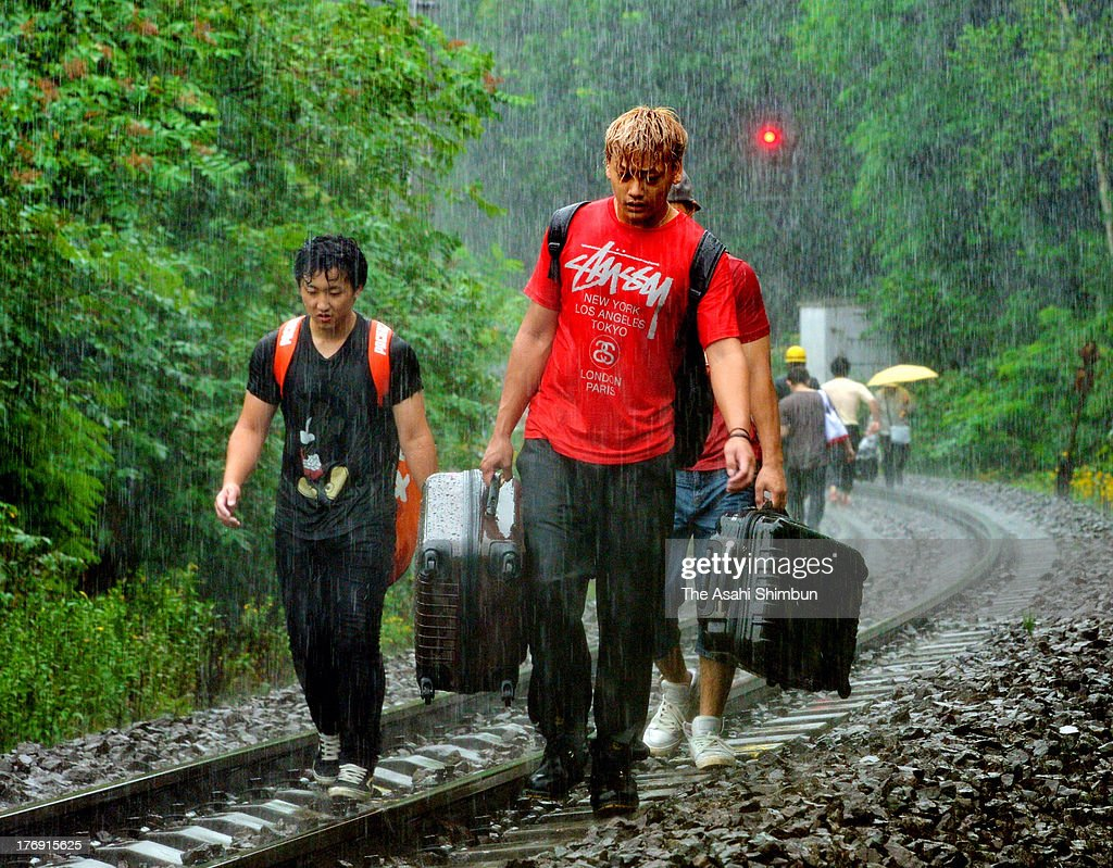 Passengers walk on the railway track on August 18, 2013 in Mori, Hokkaido, Japan. Train operation between Sapporo and Hakodate has been suspended due to a landslide triggered by a torrential rain washed the enbankment, hit 'bon' holidaymakers.