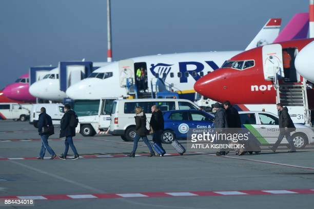 Passengers walk on the tarmac upon their arrival on December 1 2017 at the Liszt Ferenc international Airport in the Hungarian capital Budapest / AFP...