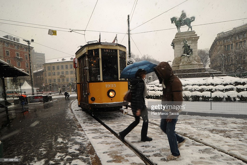 Passengers walk out from a tramway as snow falls in Milan, on February 11, 2013 in Milan, Italy.Wind, snow and tempetarture under zero over the country has affected regions from North Italy to South Italy, transports has been affected with train cancellations and road closures.