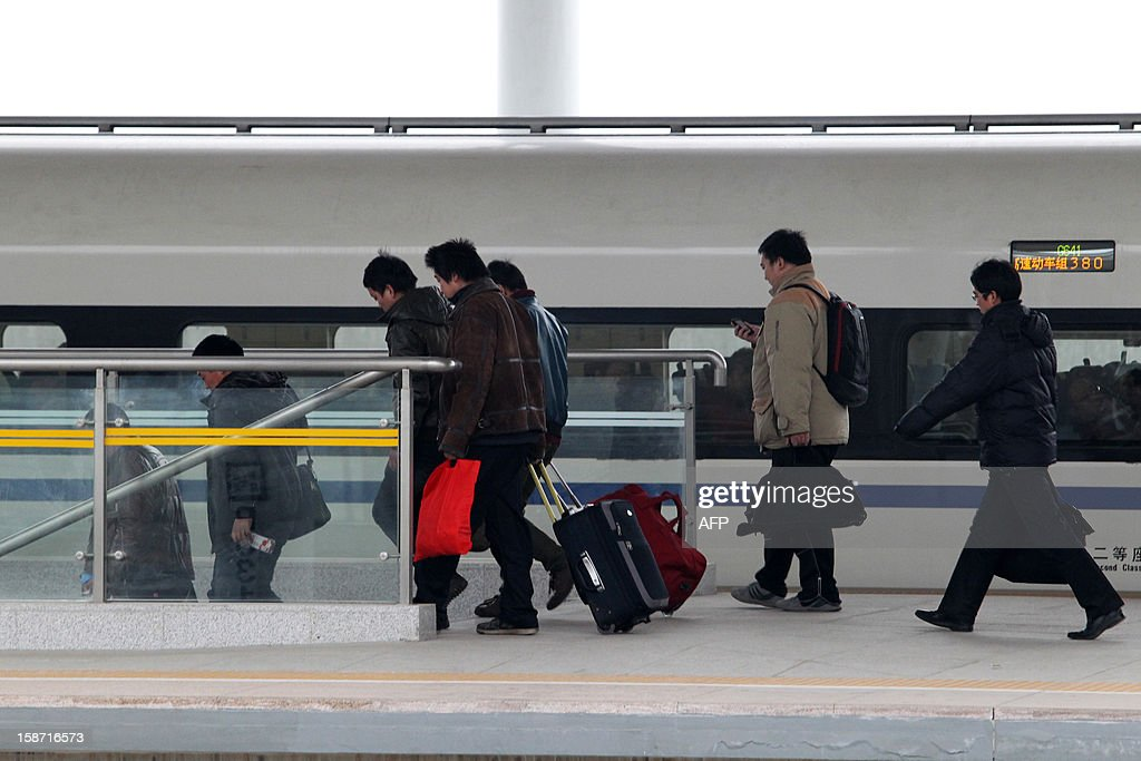 Passengers walk out of the high speed train running on the new 2,298-kilometre (1,425-mile) line between Beijing and Guangzhou in Xuchang, central China's Henan province on December 26, 2012. China started service on December 26 on the world's longest high-speed rail route, the latest milestone in the country's rapid and -- sometimes troubled -- super fast rail network. The opening of this new line means passengers will be whisked from the capital to the southern commercial hub in just eight hours, compared with the 22 hours previously required. CHINA