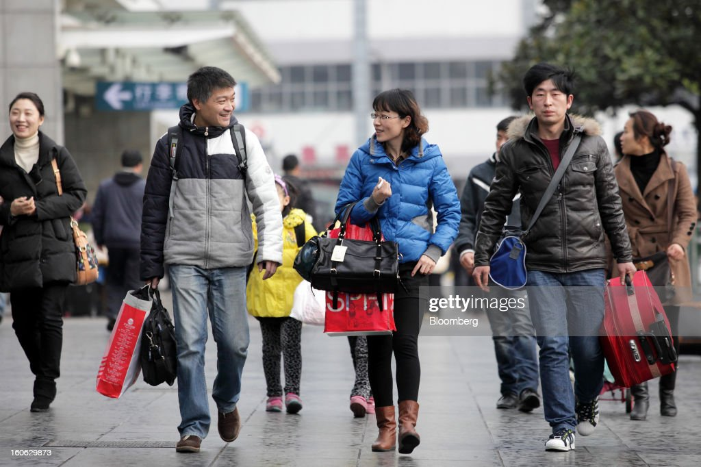 Passengers walk outside Shanghai Railway Station in Shanghai, China, on Sunday, Feb. 3, 2013. Forecasts of snow and rain across China threaten to disrupt the travel plans of millions of Chinese heading home for the Lunar New Year holidays that start Feb. 9, the national weather agency warned. Photographer: Tomohiro Ohsumi/Bloomberg via Getty Images